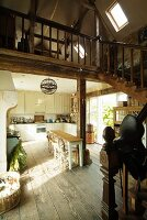 Open-plan, country-house-style living-dining room with rustic wooden floor and wooden staircase leading to mezzanine