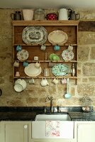 Various plates, cups and small jugs hanging from hooks on nostalgic kitchen shelving above vintage sink unit against stone wall