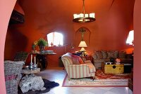 Red-painted living room in Romanesque house with sofa combination below wrought iron pendant lamp