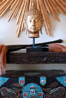 Buddha's head on carved console table below sunburst gilt frame on wall