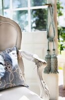 White-painted armrest of upholstered Rococo chair with floral cushions; tassels on terrace door handle in blurred background