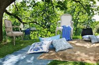 Stylish picnic area in shades of pastel blue and beige with inviting cushions, blankets and Rococo chairs next to garden table