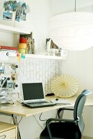 Work station with large paper lampshade above curved desk