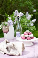 Garden table with lilac linen tablecloth and pink and white macaroons on white cake stand