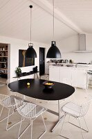 Retro hanging lamps above a dining table with black top and chairs with white metal frames in a functional kitchen