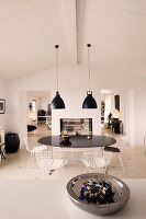 View over a counter with a bowl into a black and white dining area under retro hanging lamps