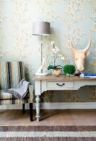 Antique country-house desk against wallpaper with delicate floral pattern contrasting with horned animal head sculpture and spiral horn as lamp base
