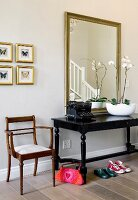 Antique furniture and old typewriter in front of mirror in hallway