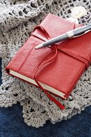 Small, leather-bound book on crocheted blanket