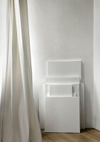Stretched white canvases of various sizes stacked against wall and white curtain at window