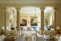 Spacious hotel lobby with classic, pale upholstered furniture and landscape paintings separated by Ionic stone pillars