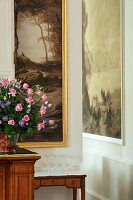Upturned wine glasses on small antique table and bouquet of roses in front of large landscape painting in elegant hotel lobby