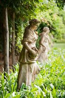 Statue of girl in flowing gown with basket of flowers in row of antique statuary amongst luxuriant green of romantic hotel gardens