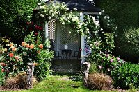 Open summerhouse covered in climbing roses in flowering garden