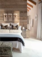 An assortment of decorative pillows and bolsters on double bed against a rustic, wood plank wall serving as a room divider and floor to ceiling opening to the en suite