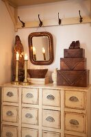 Candlesticks & wooden ornaments on apothecary cabinet