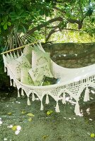 Cosy garden corner - hammock with cushions in front of garden wall
