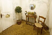 Simple bathroom with vintage washstand and potted tree on terrazzo floor