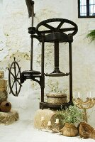 Vintage olive press and various candlesticks on floor against wall of Mediterranean farm house