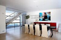 Black dining table and white-covered chairs in modern building with pale parquet floor