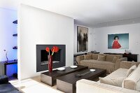 Upholstered sofas and two modern coffee tables in front of partition wall with fireplace and hidden shelving