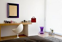 Minimalist, designer dressing table with white shell chair and blue wall-mounted mirror