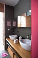 Modern, designer washstand with two wash basins below wide, mirrored cabinet