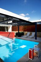 Roof made of metal girders and glass above designer pool on terrace of modern apartment building
