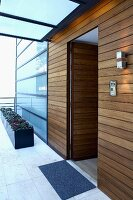Wood-panelled foyer of modern apartment building with frosted glass facade