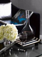Red wine and vase of hydrangeas on side table in living room