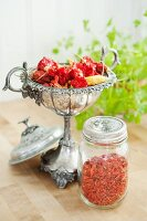 Dried chilli peppers in silver dish and jar of goji berries
