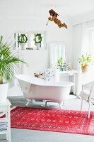 White bathroom with free-standing bathtub and cherub figurine