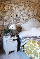 White-painted vintage bed and bedside cabinet against rustic stone wall