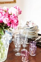 Stacked plates, various glasses and bouquet of peonies on wooden table