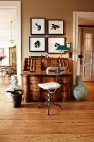 Antique bureau and retro chair against wall between two doorways in renovated, period building