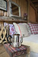 Silver teapot and book on rustic bedside table next to bed