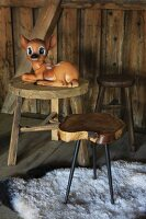 Bambi figurine on wooden stool in cabin