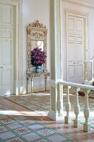 Balustrade, painted wooden column and tall doors with gilt ornamentation in foyer of stately home