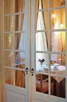 View of set breakfast table below window with gathered curtains through double interior doors with lattice windows