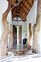 Rustic wooden supports in airy entrance hall with high wood-beamed ceiling