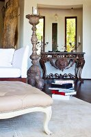 Grand, floor-standing candlestick in living room with Baroque console table made from rusty metal