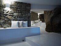 Meandering interior with cushions on masonry benches along two stone walls