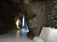 Interior with rough, unhewn rock walls and bench with white cushions against rustic stone wall