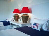 Modern bedroom with patriotic atmosphere - table lamps with red lampshades on bedside table between twin beds and Stars and Stripes cushions