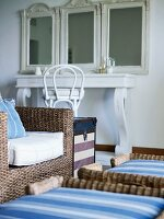 Rattan armchair with white seat cushion in front of dressing table with antique mirrors