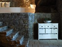 Cellar-style foyer with steps and open-fronted, half-height, retro-style cabinet against stone wall