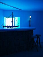 Model ship on bar and bar stools bathed in blue light