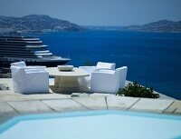 Armchairs with white covers on open-air terrace with panoramic sea view