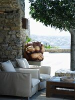 Upholstered armchairs and coffee table next to sculpture on Mediterranean terrace