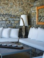 Bench with white cushions in corner of rustic room with stone walls